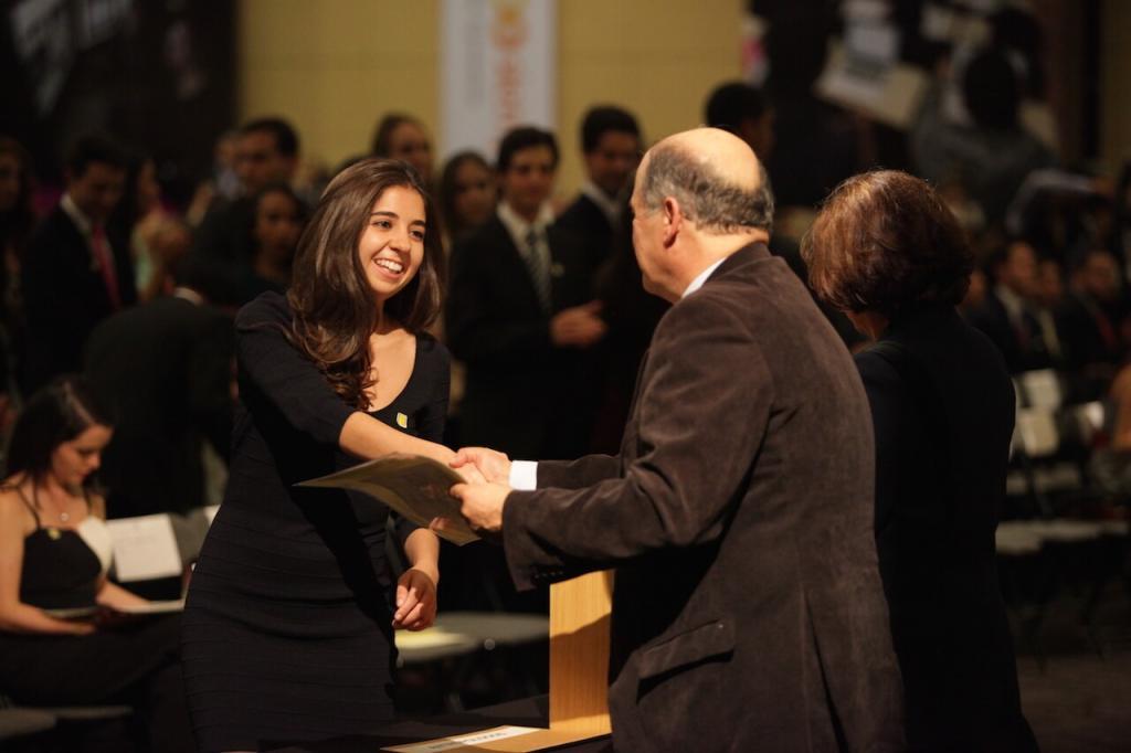 mujer de cabello largo y vestido negro estrecha la mano de un hombre que también le entrega un diploma de grado