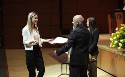 Estudiante recibe diploma de posgrado de mano de dos personas