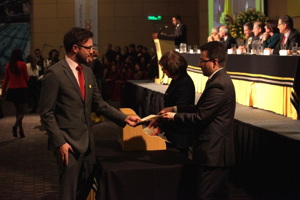 un joven de traje gris y corbata azul recibe diploma de grado