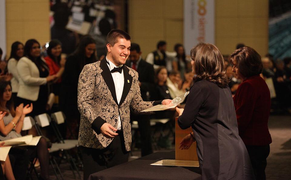 joven con chaqueta de flores y corbatín recibe diploma de grado