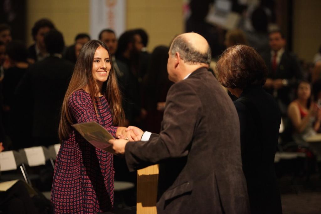 mujer de cabello largo, vestido azul con girasoles recibe diploma de grado