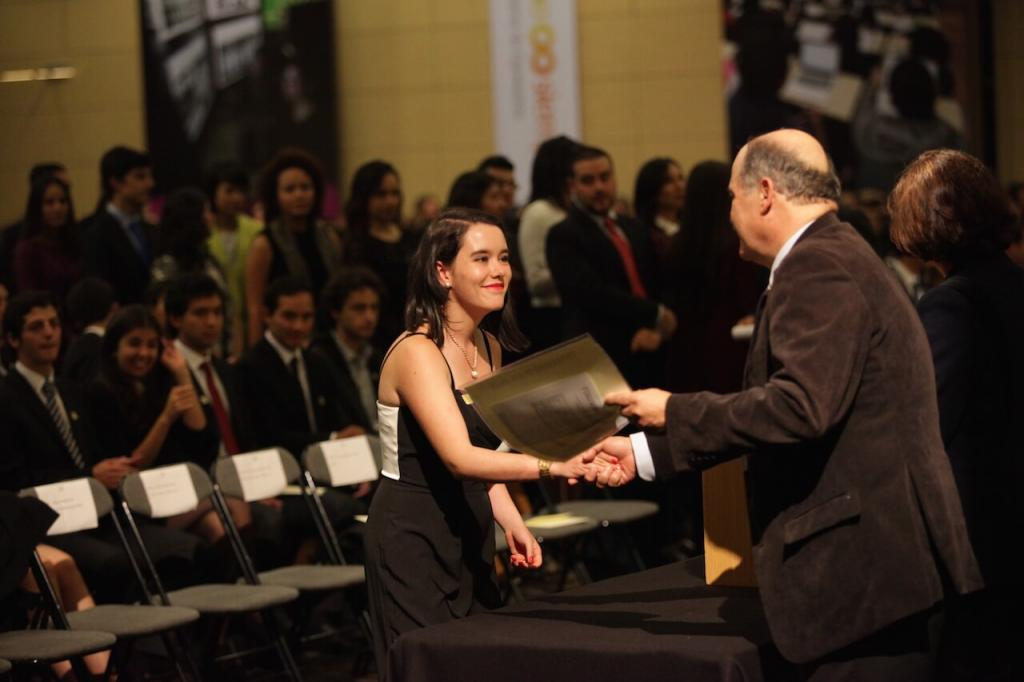 una joven con vestido blanco y negro recibe diploma de grado