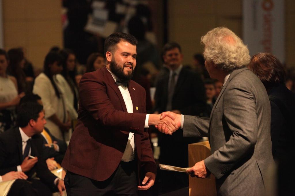 un joven de saco vinotinto recibe diploma y da la mano a un hombre mayor