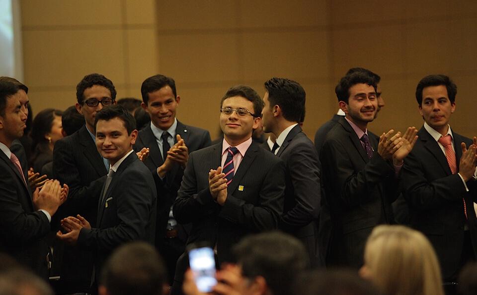 grupo de hombres aplauden a sus compañeros en ceremonia de grados