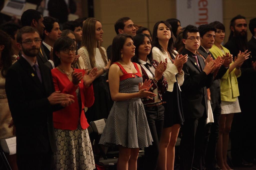 jóvenes en un auditorio aplauden en una ceremonia de grados