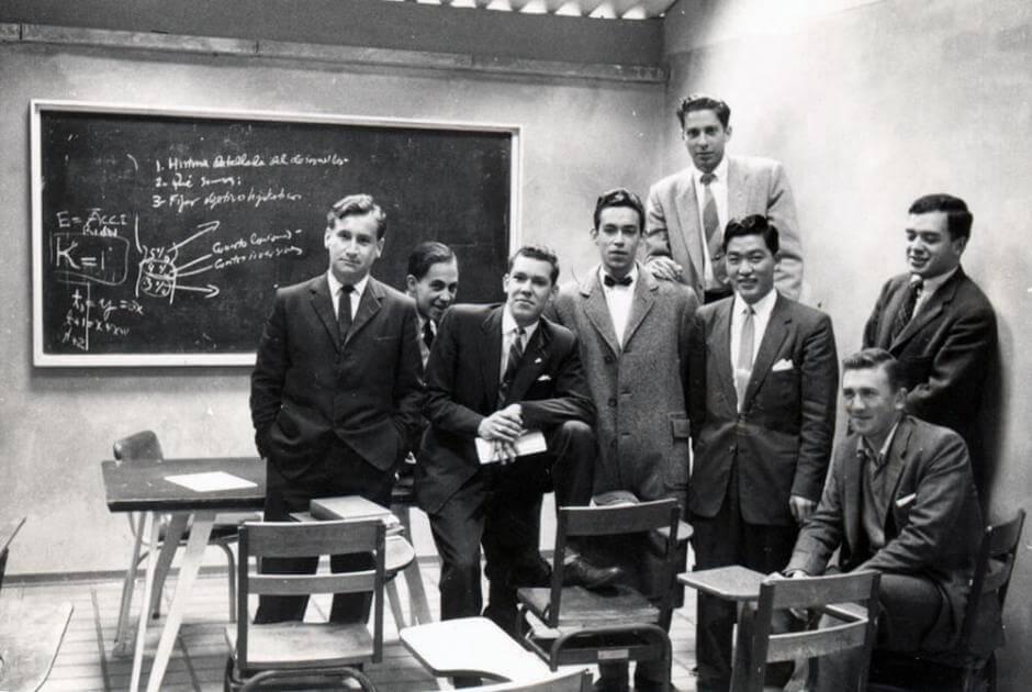 varios estudiantes en un salon posan para la foto, algunos están sentados en los pupitres, otros están de pie. La foto es antigua y en blanco y negro
