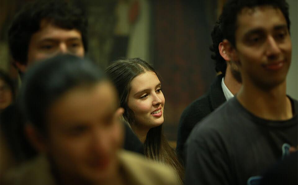 rostro de una estudiante sonriendo en medio de más personas en un salón