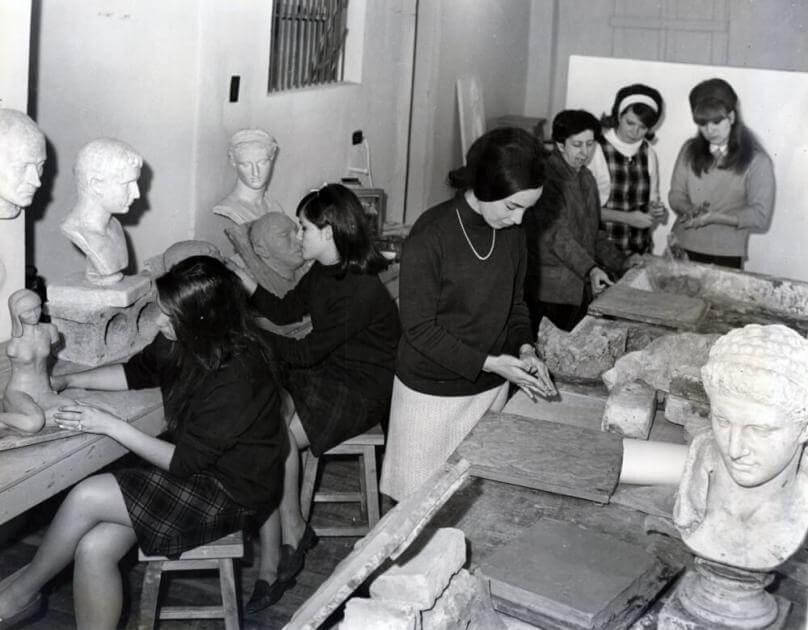 mujeres trabajando en un taller de artes plásticas, se ven las esculturas que tienen en sus manos. La foto es antigua y en blanco y negro