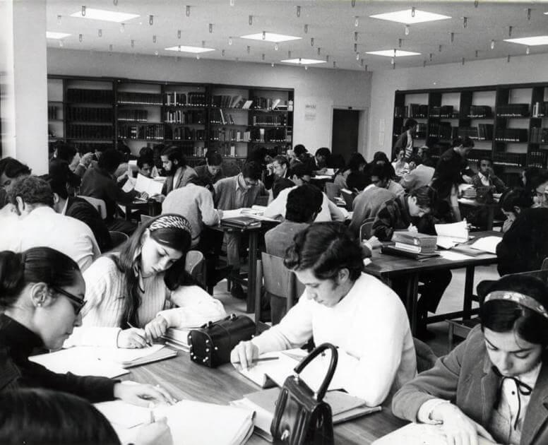 foto antigua en blanco y negro de un grupo de estudiantes en las mesas de lectura de una biblioteca
