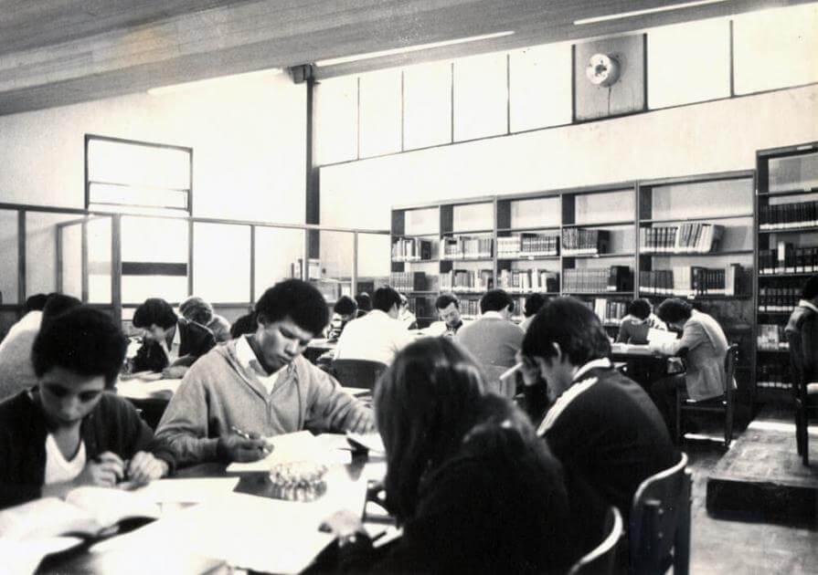 foto antigua en blanco y negro de grupo de estudiantes en las mesas de lectura de una biblioteca