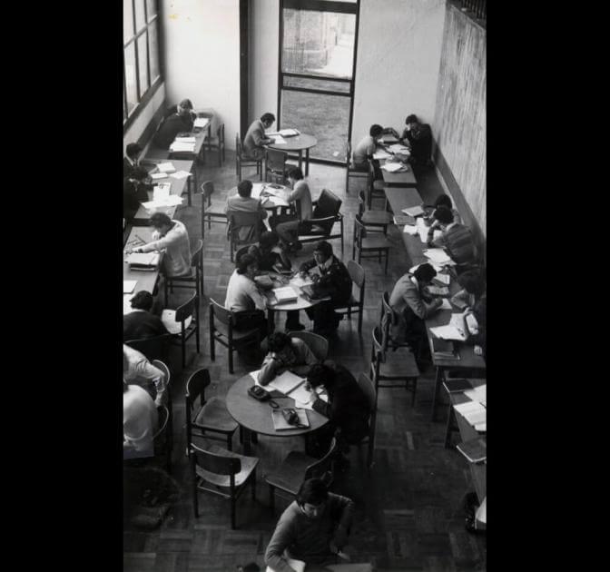 Foto antigua en blanco y negro, desde un segundo piso se ve una sala con mesas y estudiantes en ellas