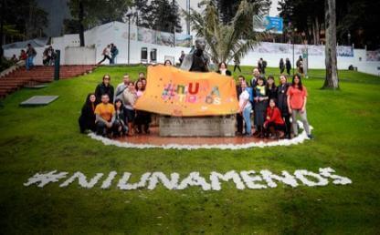 estudiantes en campo con pancarta en contra de la violencia y el maltrato a la mujer