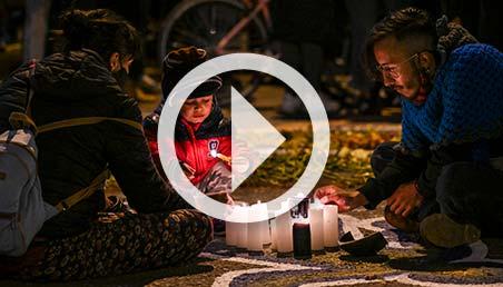 Una familia prende velas.