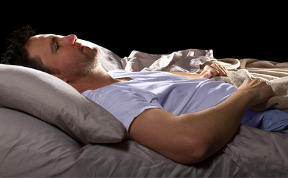 Man lying in bed with insomnia