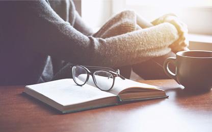 Mujer sentada mirando a través de una ventana, con libro y café