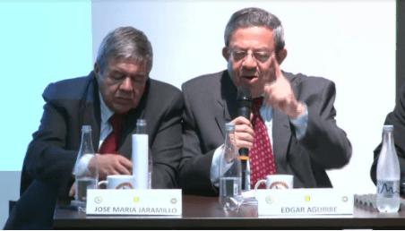 Dos hombres encorbatados en una mesa de conversatorio hablan sobre Fracking en Colombia