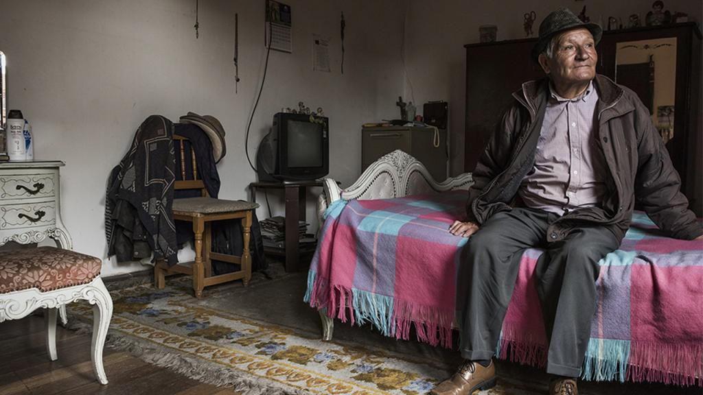 Foto de señor sentado en la cama viendo al horizonte