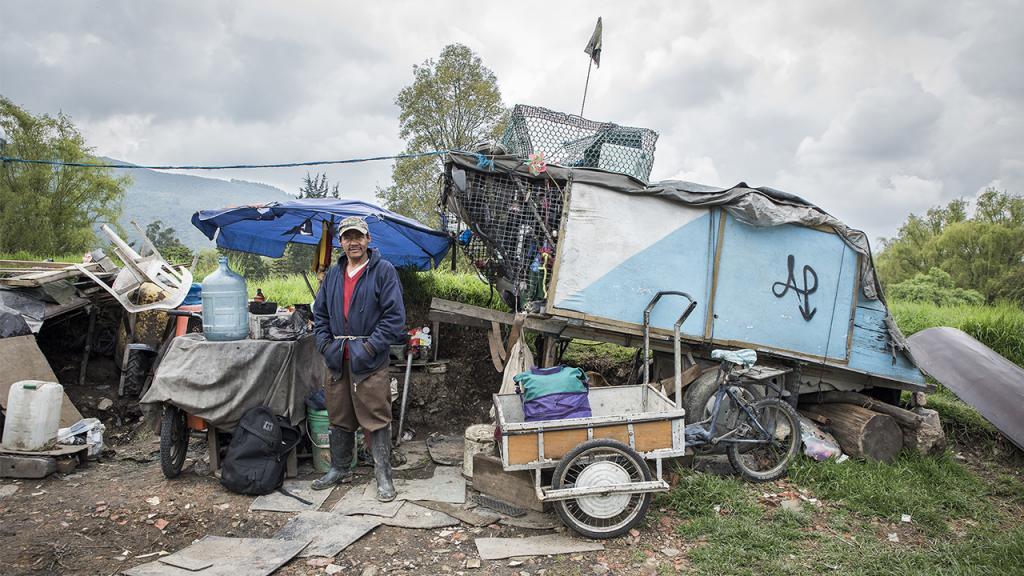 Foto de un hombre junto a una carreta de reciclaje