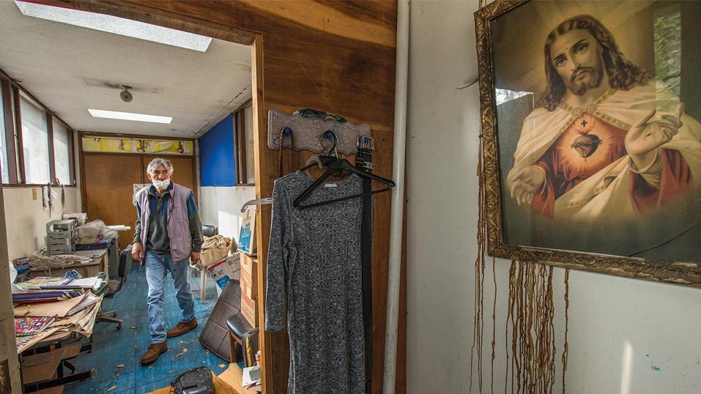 Foto de un señor en un espacio desordenado, en la pared un cuadro del sagrado Corazón de Jesús