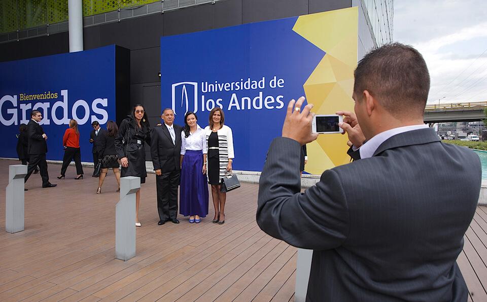 un hombre toma una foto a una familia junto a un aviso de la universidad de los andes