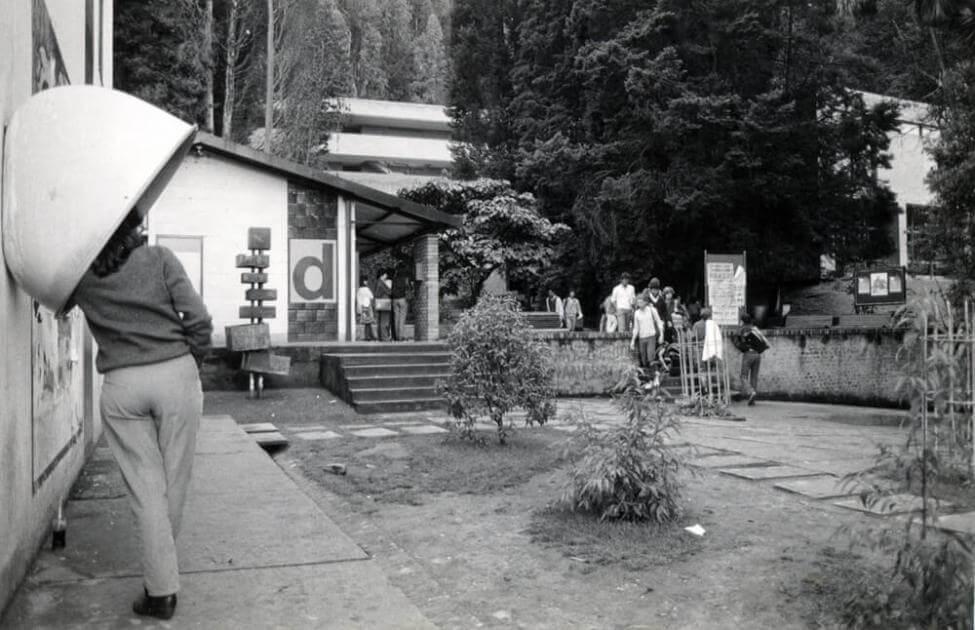 foto antigua en blanco y negro, una mujer habla por un teléfono público y se ve un campo abierto junto a un edificio con estudiantes