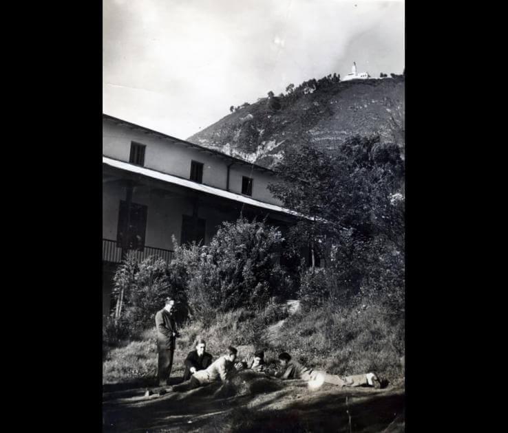 foto antigua en blanco y negro del exterior de un edificio, al fondo se ve el cerro de Monserrate