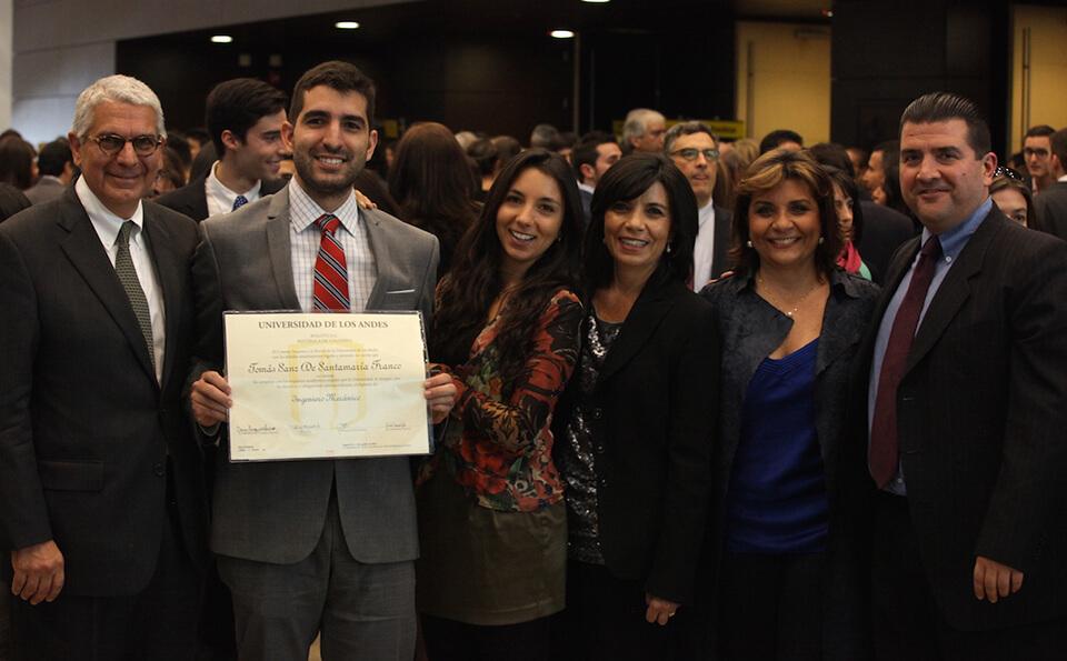 una familia posa para una foto en la celebración de un joven mostrando su diploma