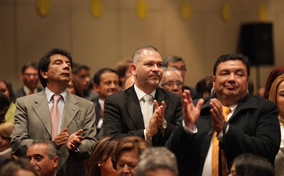 tres hombres en un auditorio, aplauden en una ceremonia