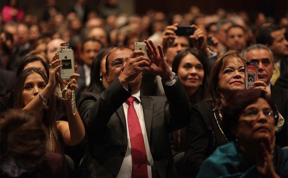 varias personas tomando fotos en un auditorio