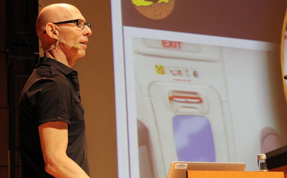 hombre calvo con camiseta negra da conferencia en auditorio