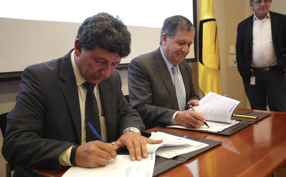 Dos hombres firmando documentos