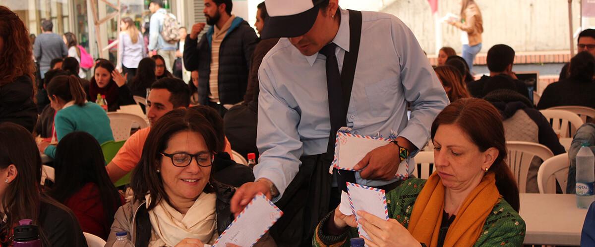 Carteros entregan cartas de agradecimiento a los participantes del Fopre Café, escritas por estudiantes becados que se benefician del Fondo de Programas Especiales