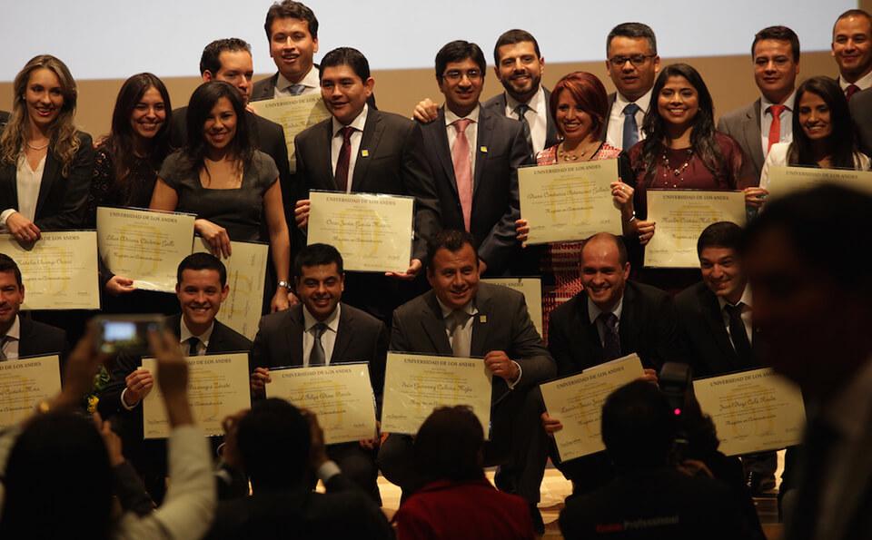grupo de personas posa para una foto, cada uno exhibiendo su diplomas