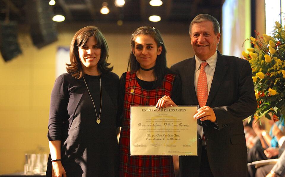 una joven de vestido de cuadros muestra su diploma de grado junto a un hombre y una mujer