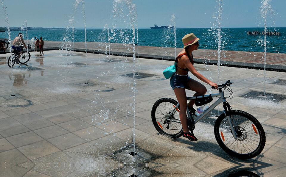 Una mujer va en bicicleta atravesando una fuente, al fondo vemos el mar, es una día soleado