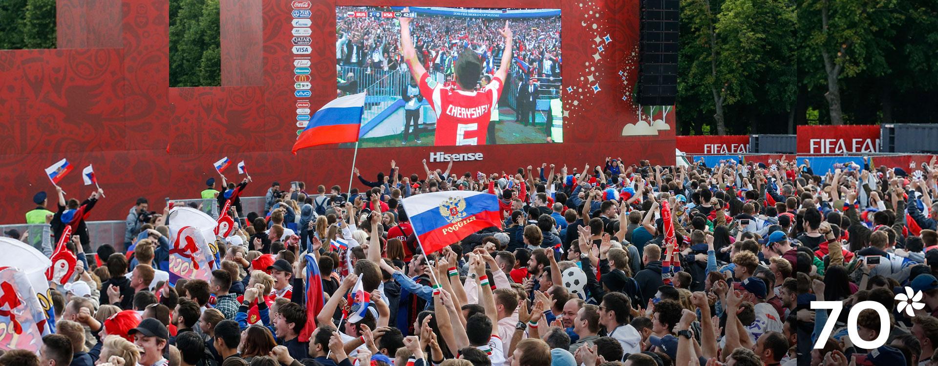 Imagen de hinchas de fútbol viendo un partido de fútbol en pantalla grande