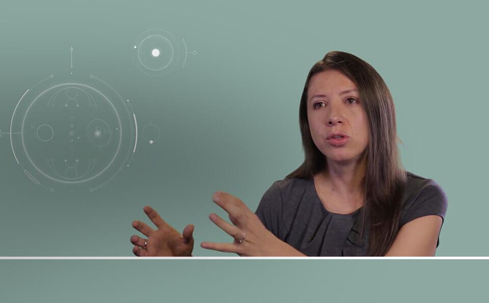 Mujer con blusa gris habla, su fondo es una animación con gráficas de ingeniería