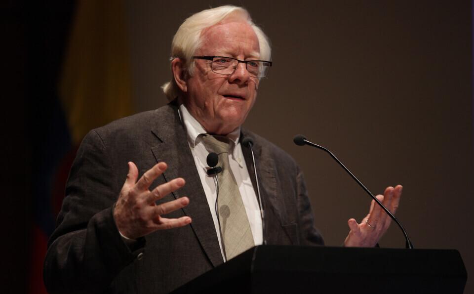 hombre mayor dando conferencia en un auditorio, lo vemos parado frente al atril