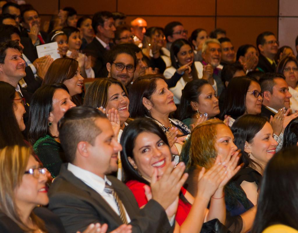 Asistentes a ceremonia de grados aplaudiendo