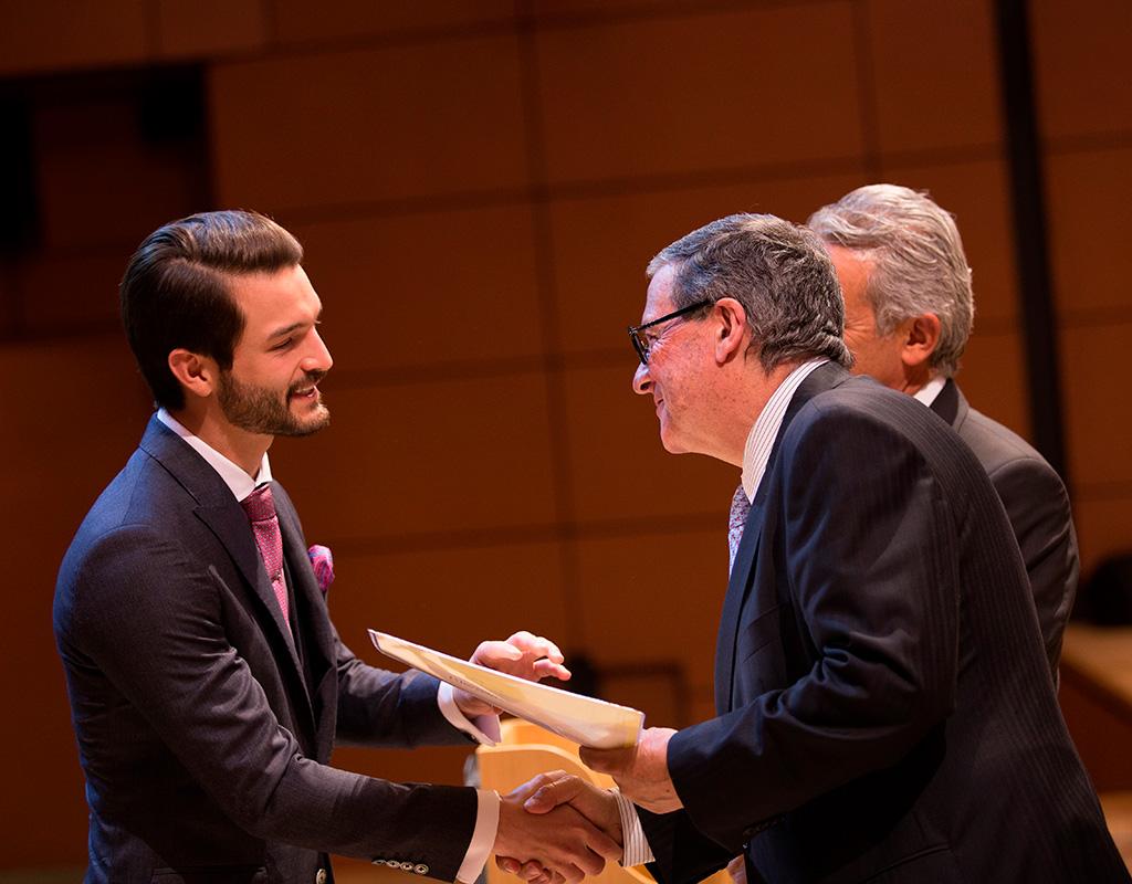 Graduando recibiendo de manos del Rector, Pablo Navas, el diploma en la ceremonia de grados 2018-1.