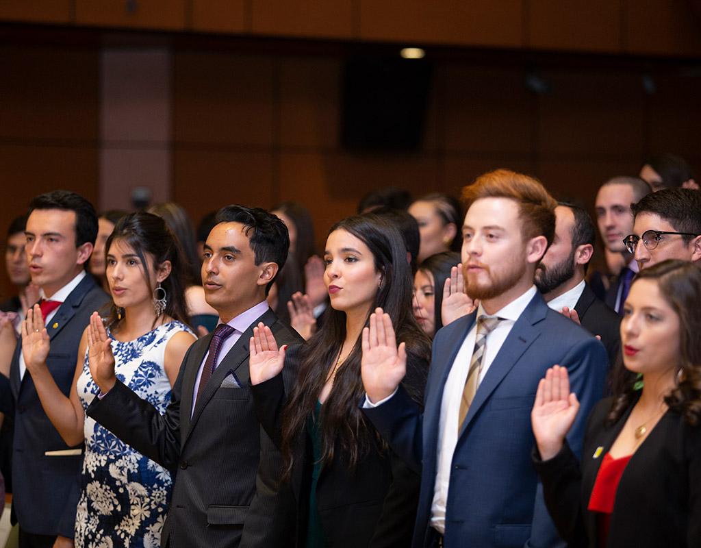 Graduandos de medicina Uniandes sostienen la mano levantada como símbolo de juramento.
