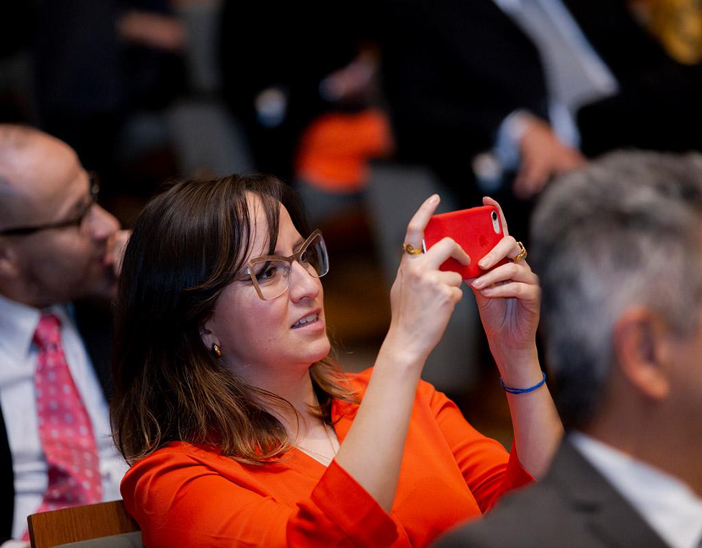 Mujer toma fotografía con su celular durante ceremonia de grados Uniandes.