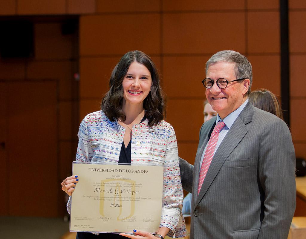 Graduanda posa con su diploma junto al rector de la Universidad de los Andes