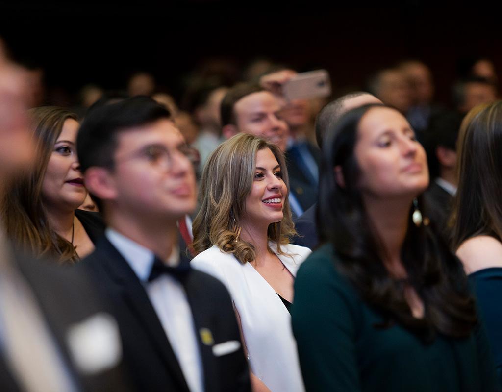Estudiantes de pie en auditorio durante grados Uniandes.