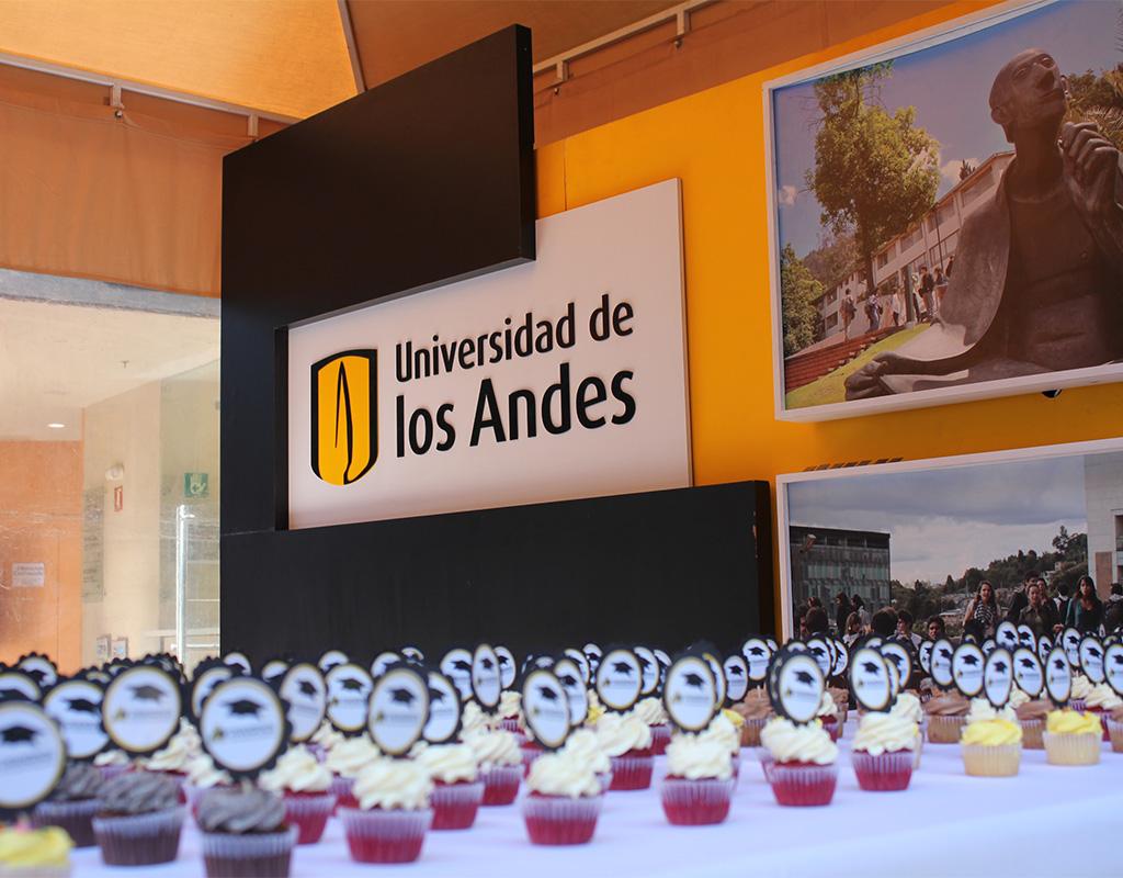 Ponqués sobre una mesa con fonde del logo Uniandes