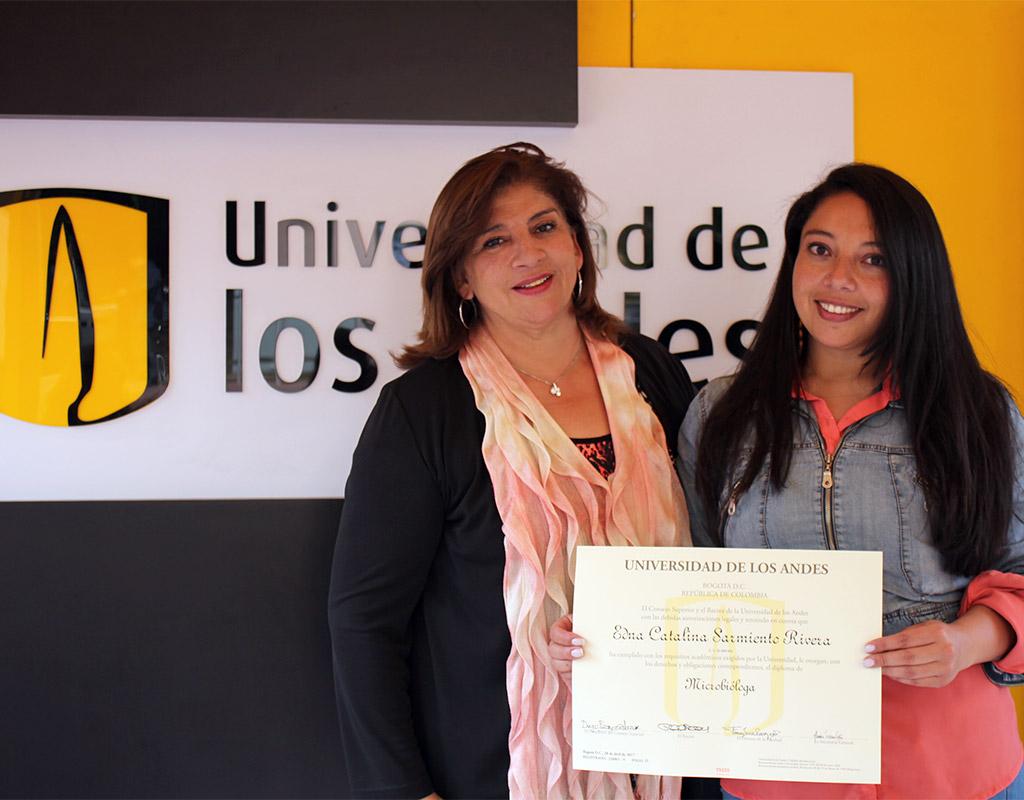 Graduanda y su mamá posan con el diploma de grado para una foto