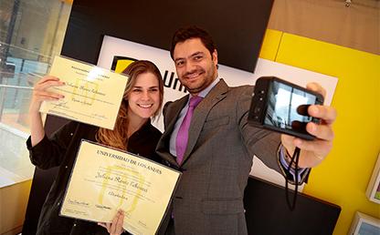Vicerrector de Desarrollo y egresados Uniandes tomando selfie con graduanda