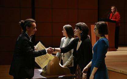 Graduando recibe diploma de manos de la Decana de la Facultad de Artes y Humanidades en el auditorio Mario Laserna