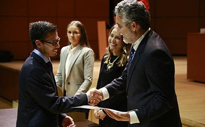 Graduando recibe diploma de manos de Juan Camilo Cárdenas, decano de la Facultad de Economía, en el auditorio Mario Laserna