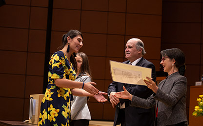 Foto de graduando recibiendo diploma de grado en auditorio de la Universidad de los Andes